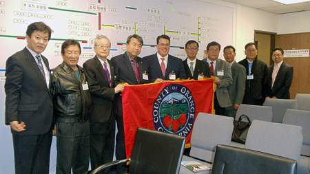 Supervisor Nelson presents the Korean American Sports Association of Orange County with an offical Orange County Flag