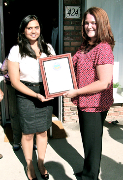 Nelson staffer Neha Sata presents Sprouts Photography in Fullerton with a Certificate for their Ribbon Cutting.