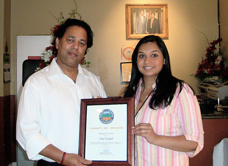 Nelson Staffer Neha Sata presenting Neel Kamal owner with a Certificate of Recognition