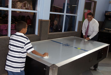 Supervisor Nelson took a moment to play a competitive air hockey game with one of the boys at the center.