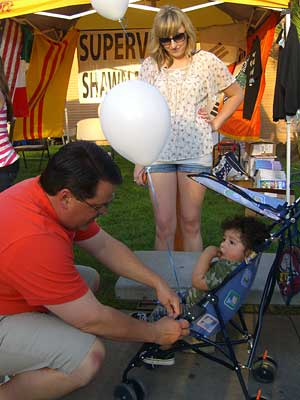 Supervisor Nelson tying ballons to a youngster's stroller.