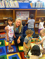Audra Adams playing with chldren in the library.